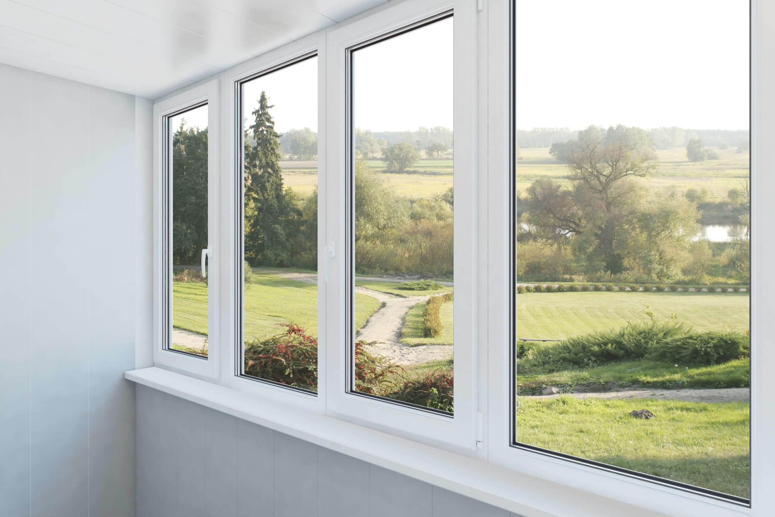 white wall with many windows and view of fields