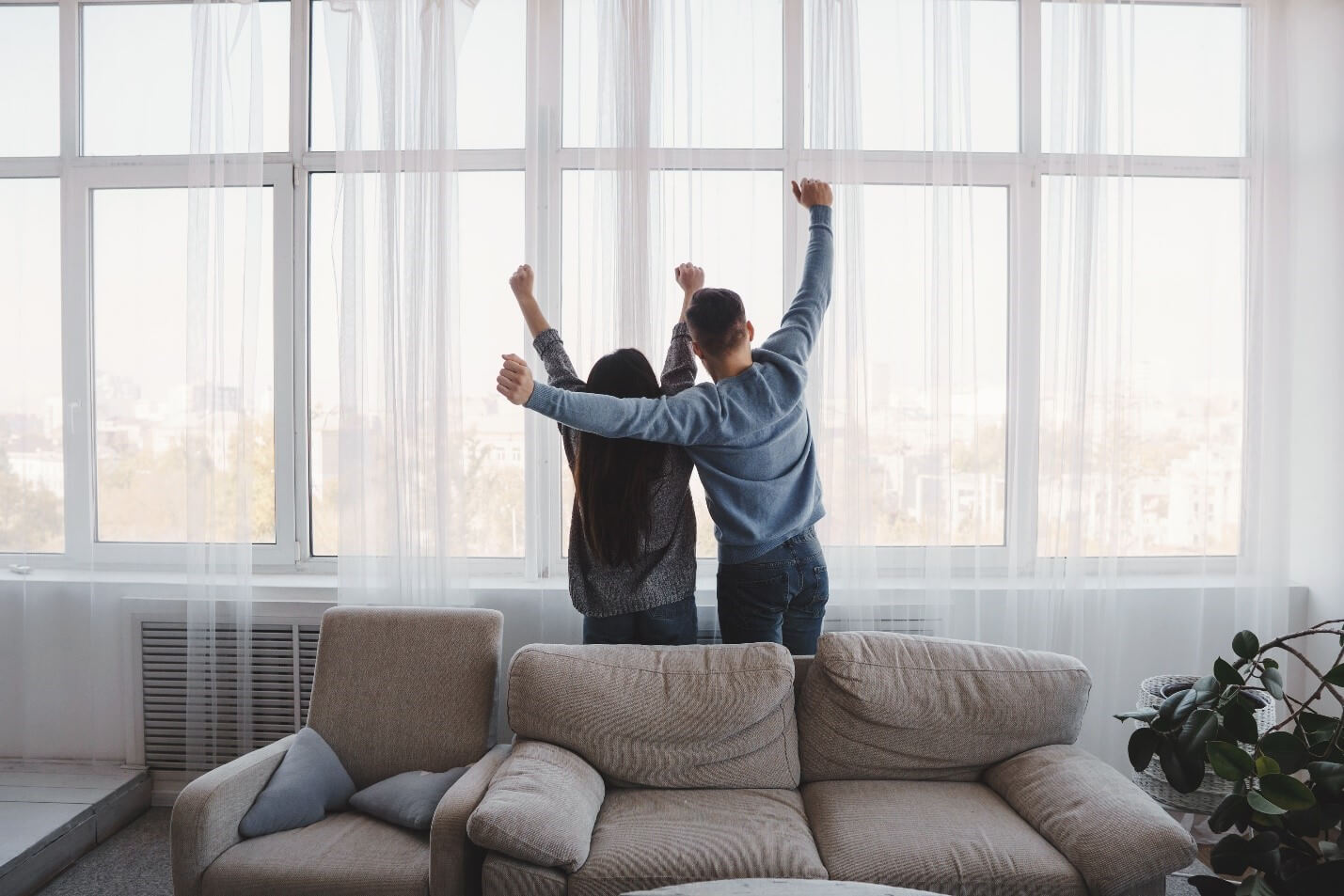 a couple standing inside big, beautiful low-e windows