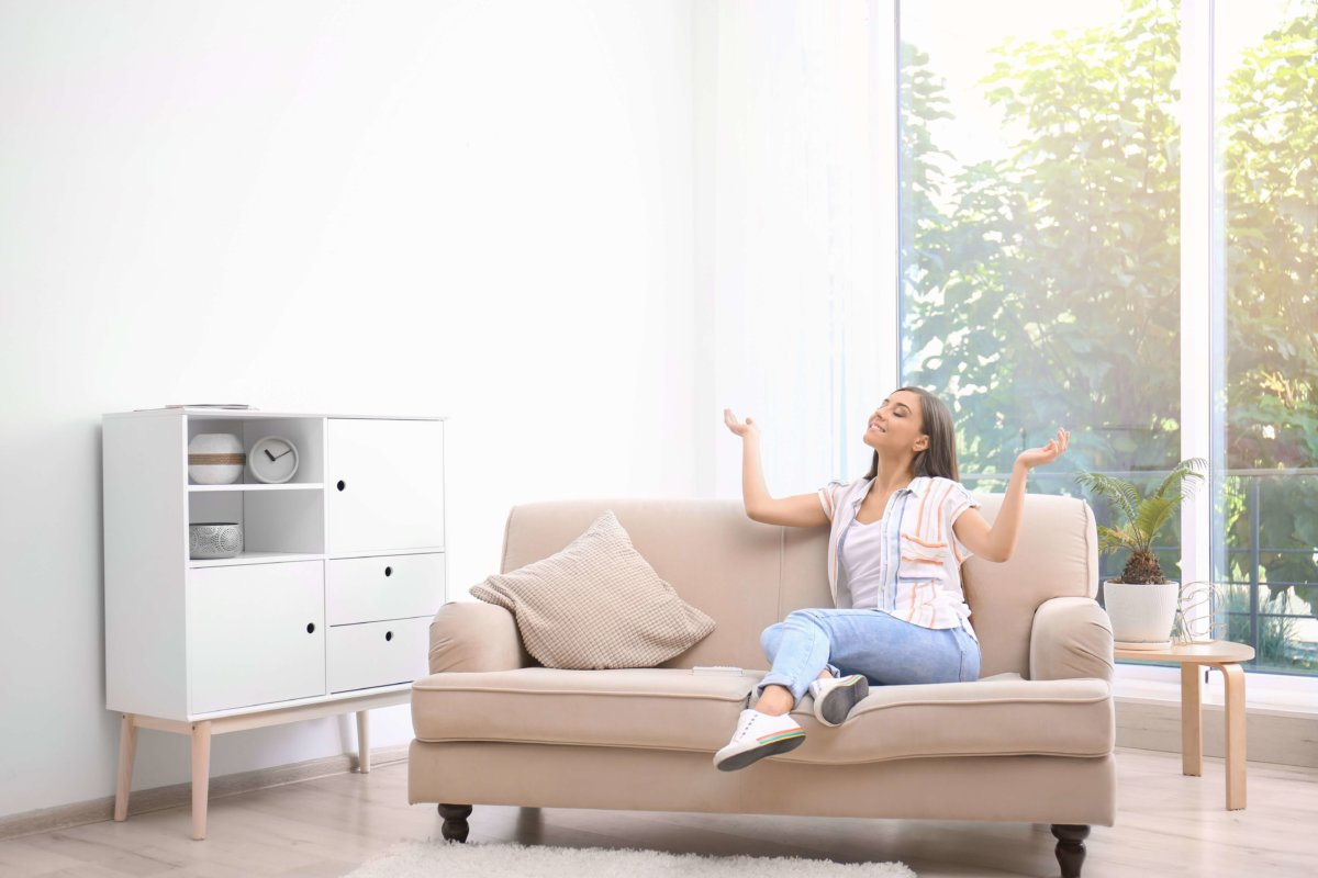 Young woman enjoys cool air in front of her living room window
