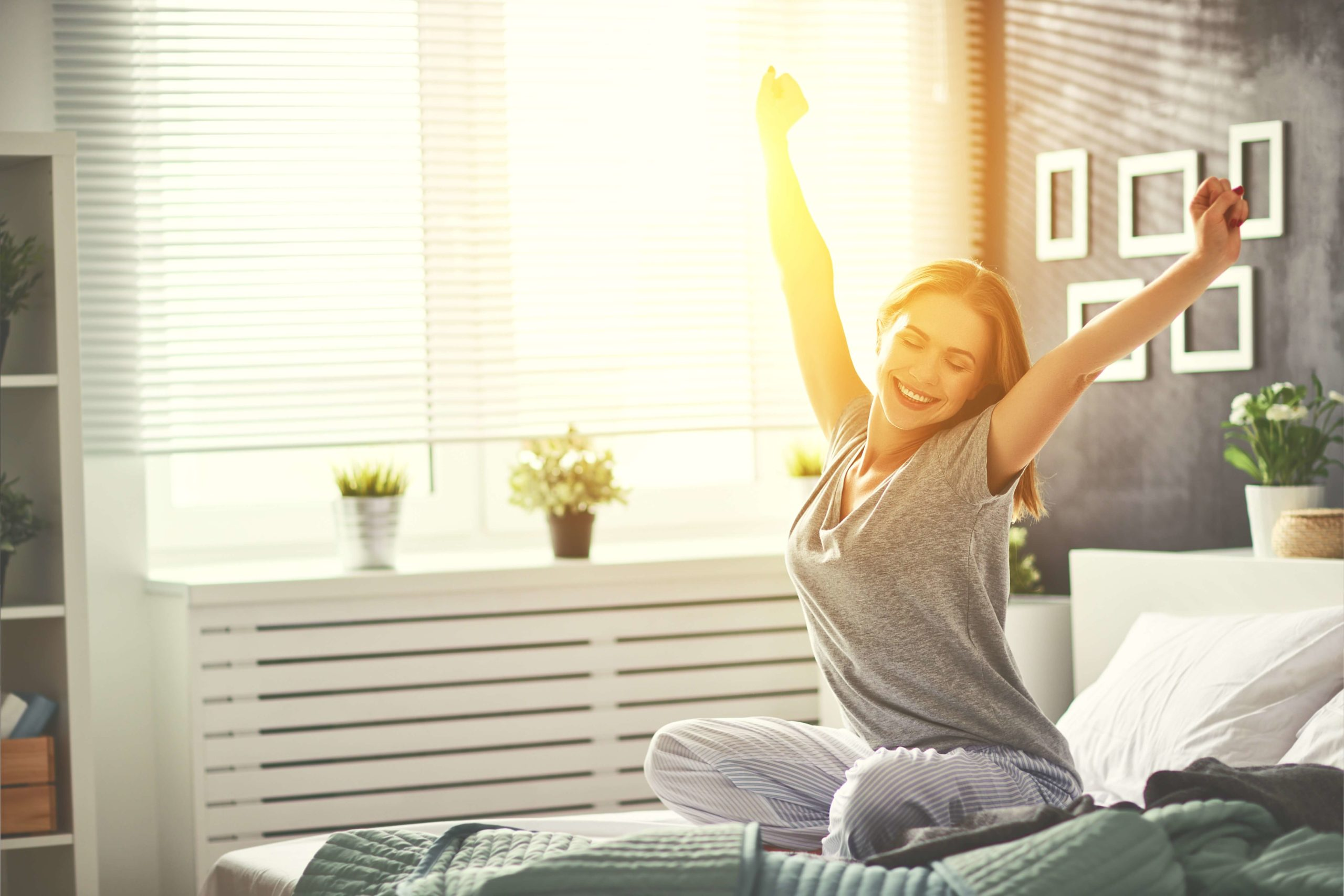 Young woman wakes up rested while sun shines in the window