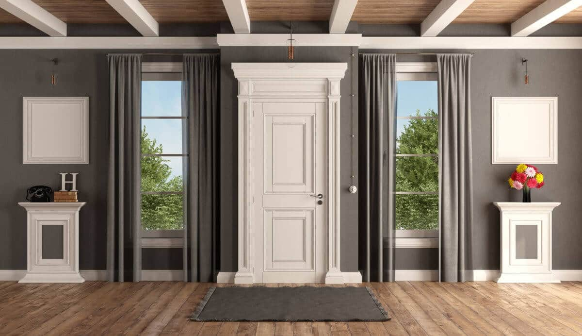 Interior shot of white front door, grey walls, and two windows