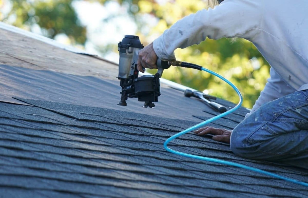 Roofer working on putting roof shingles on to replace skylights